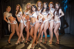 Eight beautiful showgirls posing on stage. Focus on the girl in the center stock photo
