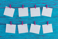 Eight blank white memo pads. Hanging from colorful wooden pink clothes pegs over an exotic turquoise blue crackle paint wooden panel in a concept of planning Royalty Free Stock Photography