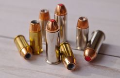 Eight bullets, five 40 caliber hollow points and and three 44 special red tipped ones stock image