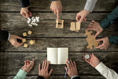 Eight businessmen planning a strategy in business advancement. Each holding  different but equally important metaphorical element - compass,  puzzle pieces Royalty Free Stock Images