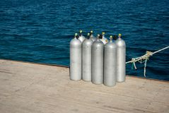 Full oxygen tanks on pier. Eight cylinders with air for diving. eight aluminum cylinders on sea dock. Eight cylinders with air for diving. eight aluminum stock images