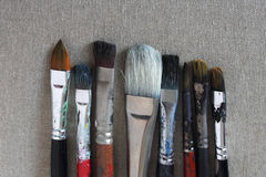 Eight dirty brushes on canvas Stock Photos