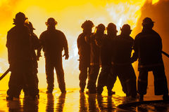 Eight firefighters during fire fighting exercise Stock Image