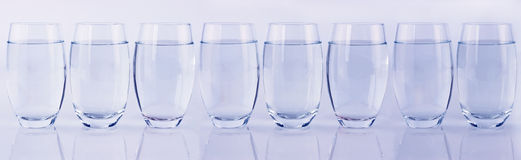 Eight glasses of water in a row Stock Image