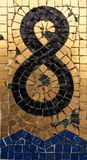 Number eight drawed with mosaic tiles. Eight in gold and black mosaic on a wall Stock Photos