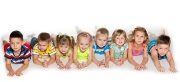 Eight kids lying on floor Royalty Free Stock Photo