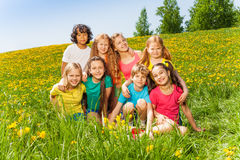 Eight kids sitting together on the green grass Stock Photo