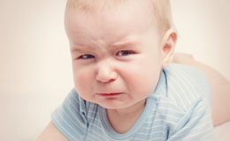 Eight month old baby crying. Sad child portrait stock photo
