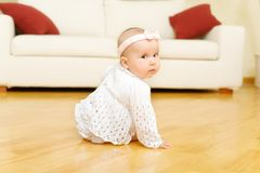 Eight month old baby girl seated on a floor Royalty Free Stock Photos