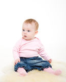 Eight-monthly girl in a pink jacket and jeans Stock Photos