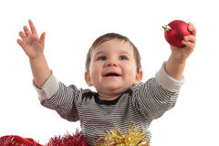 Eight months baby inside a box. Showing a christmas ball in a white background Royalty Free Stock Photos