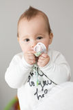 Eight months old baby girl bringing her pacifier to her mouth Royalty Free Stock Photo