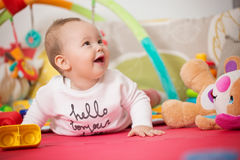 Eight months old baby girl playing with colorful toys Royalty Free Stock Photos