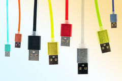 Eight multicolored usb cables hang vertically, on a gradient, tinted background. The family unites. future technologies. stock images