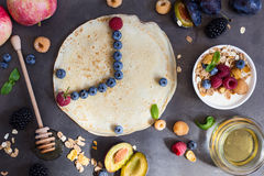 Eight o`clock in the morning, healthy breakfast. Healthy breakfast muesli and crepes with fresh berries and fruits, top view. Eight o`clock in the morning Stock Images