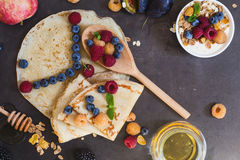 Eight o`clock in the morning, healthy breakfast. Healthy breakfast muesli and crepes with fresh berries and fruits, top view. Eight o`clock in the morning Royalty Free Stock Images