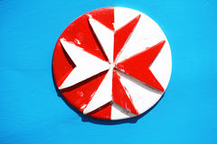 Eight pointed cross. Wooden maltese cross painted in white and red on a bright blue background Stock Photo