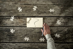 Eight puzzle pieces around question mark and hand. Eight blank puzzle pieces spaced evenly around hand written question mark near human arm holding pen over Stock Photography