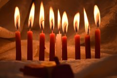 Hanukkah candles lit in the dark royalty free stock photos
