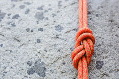 Eight rope knot on rocky background Stock Photo