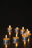 Eight small candles burning Stock Images