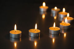 Eight small candles burning Royalty Free Stock Photos