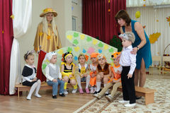 Eight small children dressed in carnival costumes and women. BALASHIKHA, RUSSIA - OCTOBER 26: Eight small children, dressed in carnival costumes, and two adult Stock Photography