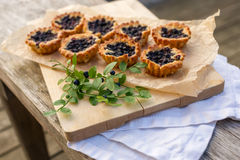 Eight small homemade blueberry pies on wooden table. Eight small and fresh blueberry pies on wooden table. Bilberry pie on top of paper and linen. Fresh and Stock Photography