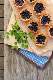 Eight small homemade blueberry pies on wooden table from top. Royalty Free Stock Photos