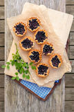 Eight small homemade blueberry pies on wooden table from top. Stock Photo