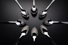 Eight stainless steel spoons on black background. Stock Photo
