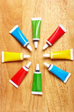 Eight tubes with food coloring. In a circle on wood Royalty Free Stock Photo