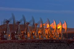 Eight Well Pad Pump Jack Blur. Eight Oil Pump Jack Blur in the Bakken oil field of North Dakota Stock Photo