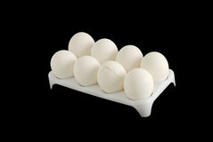 Eight white eggs with one cracked in carton Stock Photo