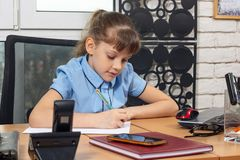 An eight-year girl writes on a sheet of paper at a table in the office royalty free stock photos