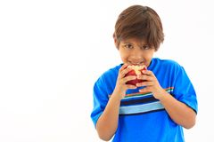 Eight year old boy biting red apple Royalty Free Stock Image