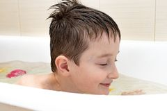 An eight year old boy sitting in bath and swimming stock images