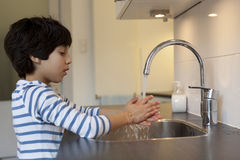 Eight year old boy washing hands. In the kitchen Royalty Free Stock Image