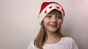 Funny caucasian girl in Santa Claus hat smiles, laughs on white background