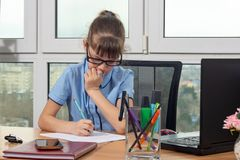 An eight-year-old girl at the table in the office thoughtfully writes a pen on a sheet of paper royalty free stock images