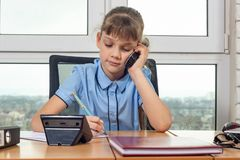Eight-year-old girl talking on the phone at the table in the office royalty free stock image