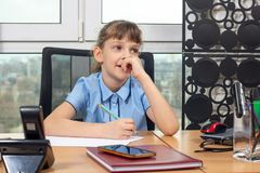 Eight-year-old girl thoughtful at the table in the office royalty free stock images