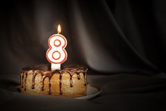 Eight years anniversary. Birthday chocolate cake with white burning candle in the form of number Eight. Dark background with black cloth royalty free stock photo