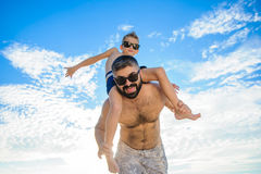 Eight years old boy sitting on dad`s shoulders. Both in swimming shorts and sunglasses, having fun on the beach. Bottom view Royalty Free Stock Photography