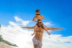 Eight years old boy sitting on dad`s shoulders. Both in swimming shorts and sunglasses, having fun on the beach. Bottom view Royalty Free Stock Images