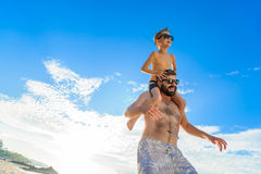 Eight years old boy sitting on dad`s shoulders. Both in swimming shorts and sunglasses, having fun on the beach. Bottom view Stock Photos