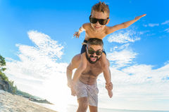 Eight years old boy sitting on dad`s shoulders. Both in swimming shorts and sunglasses, having fun on the beach. Bottom view Stock Images