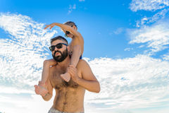 Eight years old boy sitting on dad`s shoulders. Both in swimming shorts and sunglasses, having fun on the beach. Bottom view. Blue sky and altocumulus clouds Stock Photography