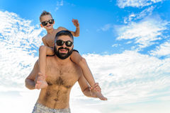 Eight years old boy sitting on dad`s shoulders. Both in swimming shorts and sunglasses, having fun on the beach. Bottom view Royalty Free Stock Image