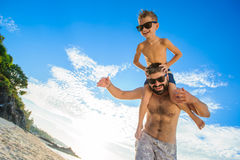 Eight years old boy sitting on dad`s shoulders. Both in swimming shorts and sunglasses, having fun on the beach. Bottom view. Blue sky and altocumulus clouds Stock Photo